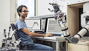 A Scientists programs a robotic arm to study motion sequences. Photo: Thomas Steuer