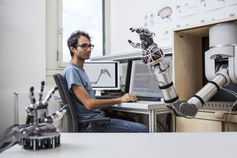 A scientist programs a robotic arm to study motion sequences. Photo: Thomas Steuer