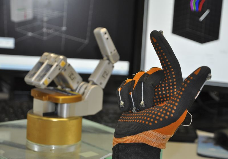 Experiment at the German Primate Center (DPZ): A data glove with magnetic fingertips measures the movements of a test person, which are then submitted to a robothand. Photo: Stefan Schaffelhofer